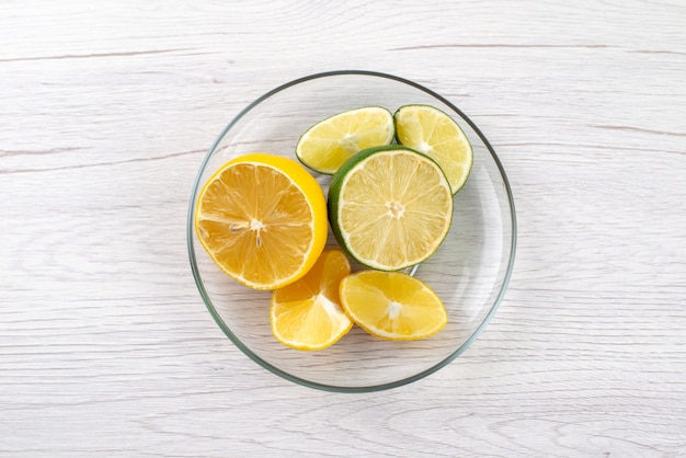 トップビュースライスした酸っぱいレモンジューシーなガラスのボウルに白い机、フルーツジュースの色