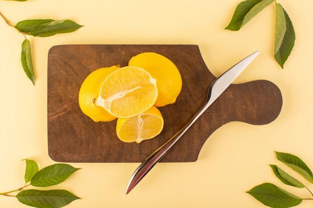 銀のナイフと茶色の木製の机とクリーム色の背景の柑橘系のオレンジ色の緑の葉と共に全体のレモンジューシーなまろやかな全体をスライスした平面図