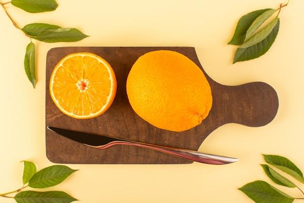 上面図は、茶色の木製の机とクリーム色の背景の柑橘系のオレンジに銀のナイフと緑の葉とともに全体のオレンジの新鮮でジューシーなまろやかさをスライスしました