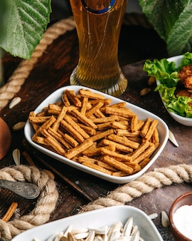 Вид сверху пряных крекеров внутри белой тарелки на деревянном столе сухарики крекера закуски