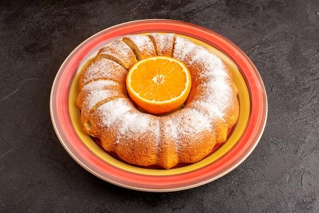 Сверху вид сладкого круглого торта с сахарной пудрой и апельсином посередине нарезанной сладкой вкусной внутренней тарелкой на сером фоне бисквитного сахарного печенья