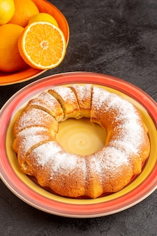 Сверху вид сладкого круглого торта с кусочками сахарной пудры, сладкого вкусного внутри тарелки вместе с апельсинами и на сером фоне бисквитного сахарного печенья