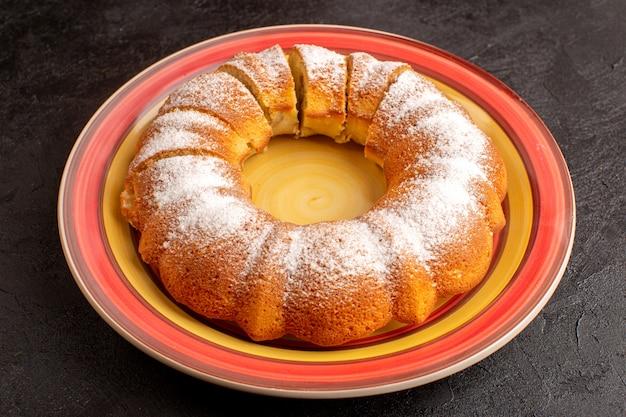 Сладкий круглый торт сверху с кусочками сахарной пудры сладкий вкусный изолированный торт внутри тарелки и серого бисквитного печенья