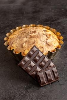 Вид сверху сладкий круглый торт вкусный вкусный внутри кекса, а также шоколадные батончики на сером фоне печенье сахарное печенье