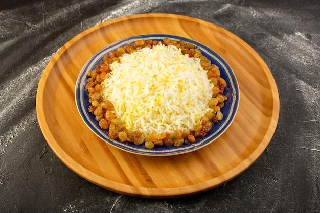Вид сверху вкусного плова с маслом и изюмом внутри тарелки на темной поверхности