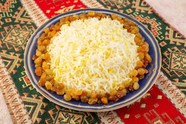 Вид сверху вкусный плов с маслом и изюмом внутри тарелки