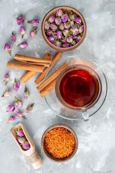 Чай с корицей и пурпурным цветком, вид сверху, повсюду на светлом столе.