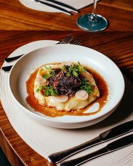 テーブルフード食事ディナーレストランでカトラリーと白いプレート内の緑と上面野菜食事