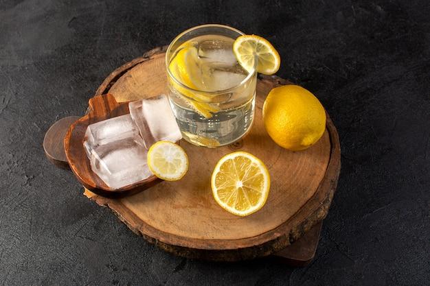 暗い背景のカクテルドリンクフルーツにスライスしたレモンのアイスキューブとグラスの中のレモン新鮮な冷たい飲み物と上面図水