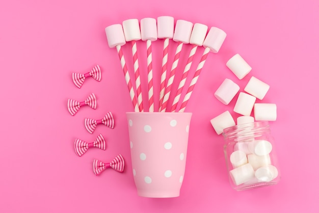 Вид сверху белый зефир с розовыми палочками и бантами на розовом столе, сладкий цвет сахара