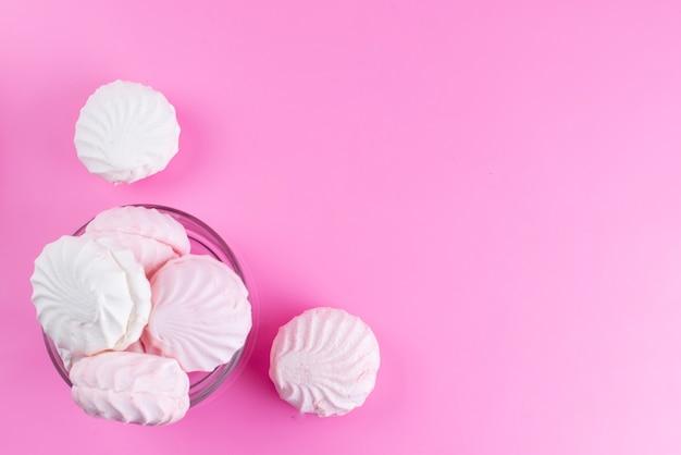 Вид сверху белые безе внутри круглой стеклянной миски на розовом