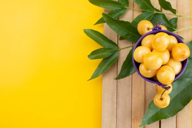 Вид сверху желтые вишни, спелые и сочные в фиолетовой корзине на желтом столе, цвет лета фруктов