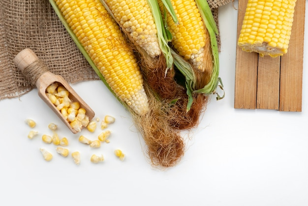 Вид сверху желтых зерен сырых с зелеными листьями на белом столе, кукуруза цвета еды