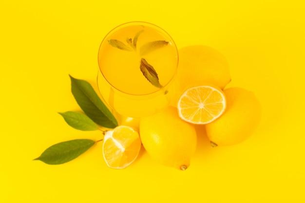 トップビュー黄色の新鮮なレモン新鮮な熟した全体と黄色の背景の柑橘系の果物の色に分離されたガラスの果物の中にレモン飲み物とスライス