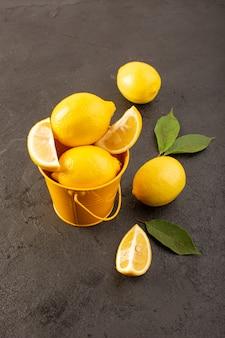 平面図黄色の新鮮なレモンのまろやかでジューシーな全体と黄色のバスケットの中にスライスされた暗い背景の果物の柑橘系の色に緑の葉が広がる