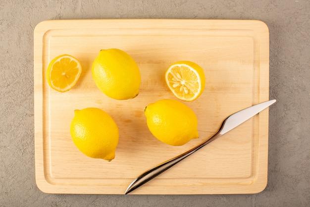 Вид сверху желтых свежих лимонов спелых сочных спелых всплыли на кремовом столе, выложенном нарезанными на сером фоне фруктами цитрусового цвета