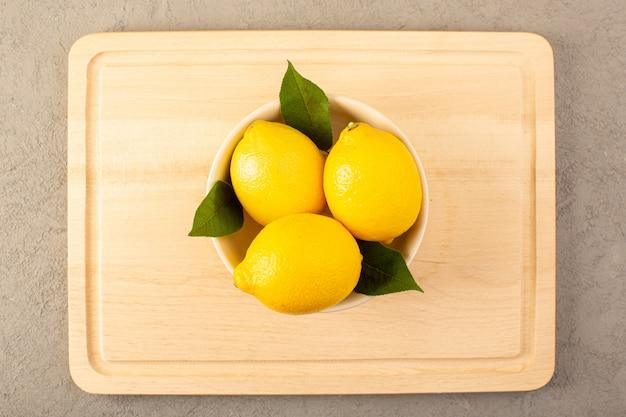 Вид сверху желтые свежие лимоны спелые сочные спелые с зелеными листьями внутри белой чаши, выложенной на сером фоне фруктов цитрусового цвета