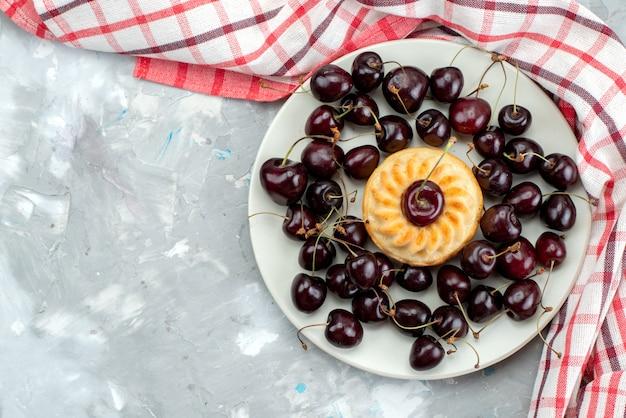 Вкусный торт с вишней внутри тарелки, печенье, сахар, фрукты, вид сверху