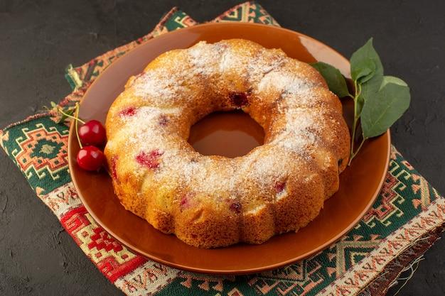 Вид сверху на вкусный вишневый торт, круглый, сформированный внутри коричневой тарелки на темном столе, торт, печенье, сахар, сладкое