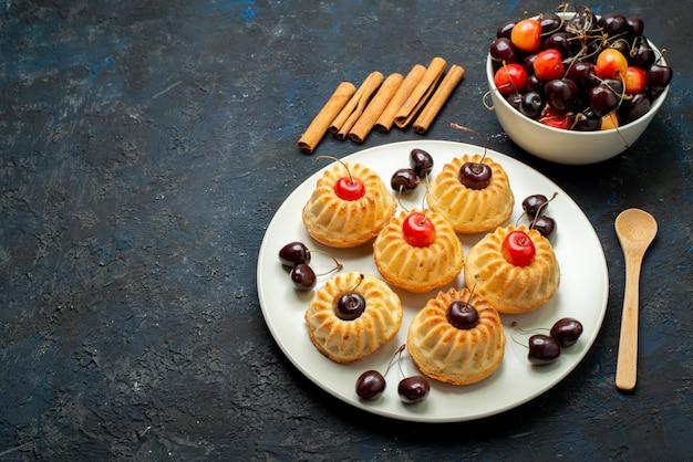 Вид сверху вкусного печенья внутри белой тарелки с вишней на темном фоне фруктовый бисквитный торт