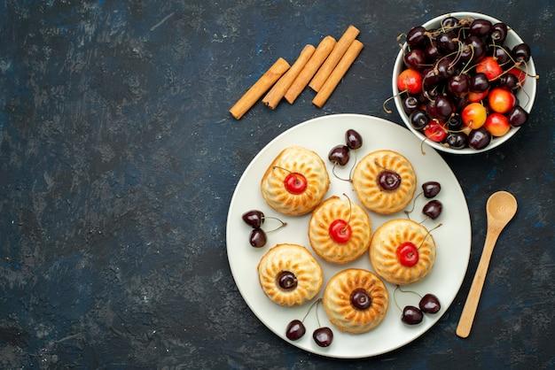 Вкусное печенье на белой тарелке с вишней на темном столе, фруктовый бисквитный торт, вид сверху
