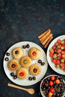 Вид сверху вкусного печенья внутри белой тарелки с вишней клубникой на темном фоне фруктовый бисквитный торт