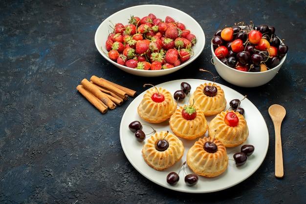 Вкусное печенье на белой тарелке с вишней и клубникой на темном столе, фруктовый бисквитный торт, вид сверху