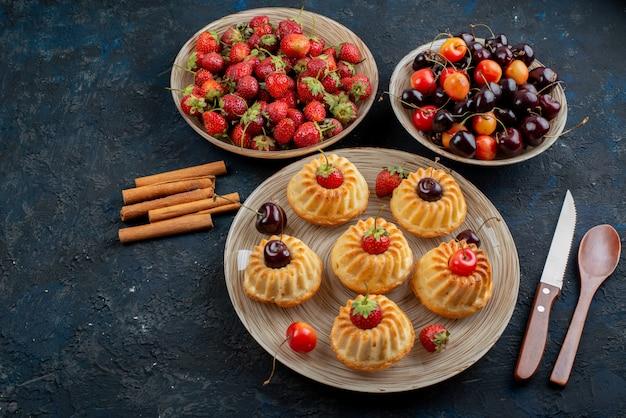 Вид сверху вкусное печенье с красной клубникой и вишней внутри тарелки на темном фоне печенья