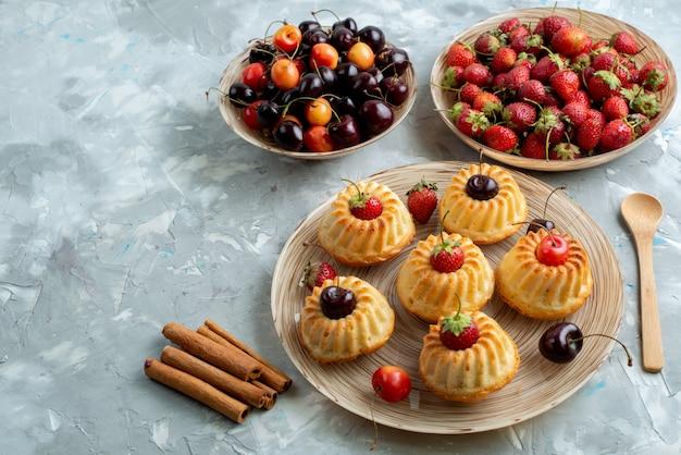 Вкусное печенье с красной клубникой и вишней внутри тарелки на темном столе, печенье, печенье, сахар, вид сверху