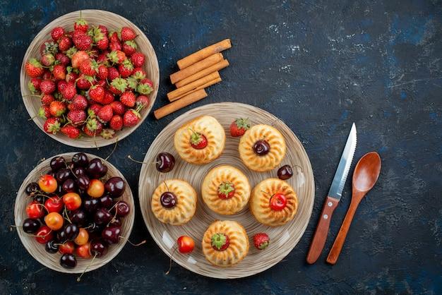 Вид сверху вкусного печенья с красной клубникой и вишней внутри тарелки на темном настольном печенье