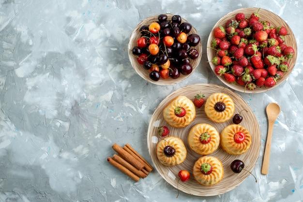 Вкусное печенье с красной клубникой и вишней внутри тарелок на темном настольном печенье, вид сверху