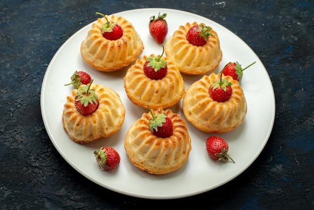 Вид сверху вкусного печенья с красной клубникой внутри белой тарелки на темном фоне печенья