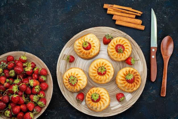 Вкусное печенье с красной клубникой на белой тарелке на темной письменной выпечке, вид сверху