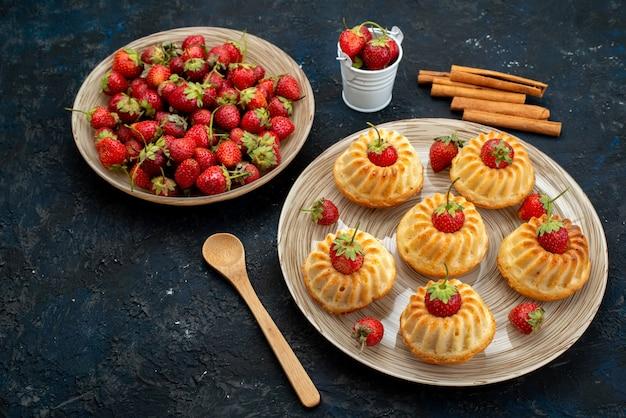 暗いデスククッキーティーの白いプレート内の赤いイチゴとトップビューおいしいクッキー