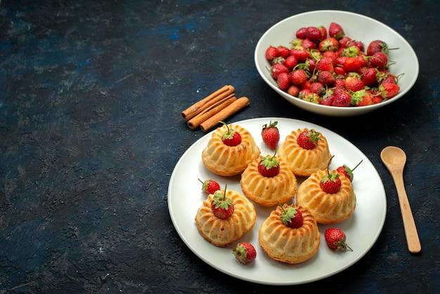 Вкусное печенье с красной клубникой на белой тарелке на темном письменном столе, вид сверху