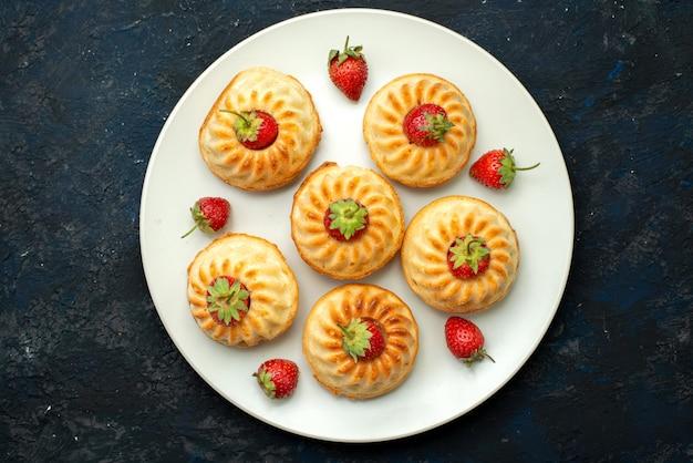 Вкусное печенье с красной клубникой на белой тарелке на темном столе, фруктовое печенье, вид сверху