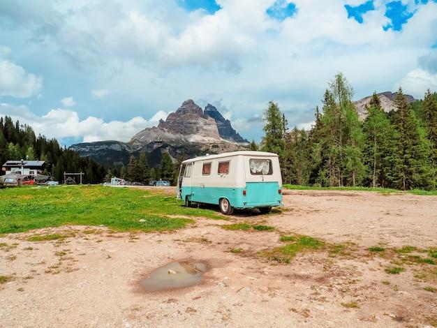 観光客の紺碧の旅行用バンは、素晴らしい風景とイタリアのドロミテ山脈に立っています