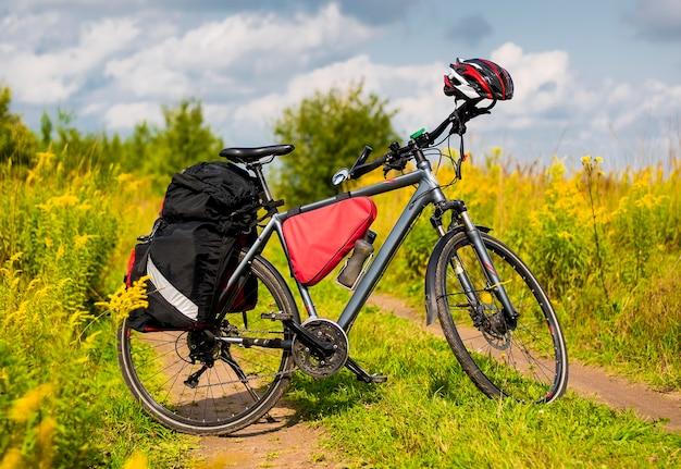 夏の緑の草や雲を背景に、ツーリストバイクが自立