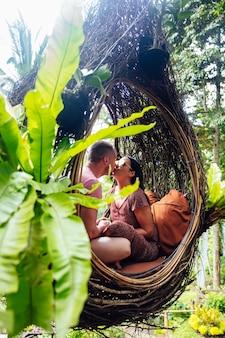 バリ島の木の大きな鳥の巣に座っている観光客のカップル