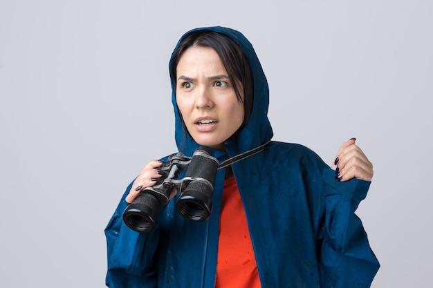 青いレインコートを着た観光客の女の子が双眼鏡を手に持って遠くを見つめているスパイ。