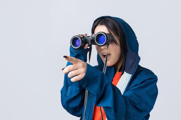 파란색 비옷을 입은 관광 소녀가 쌍안경을 손에 들고 먼 곳을 바라보고 있습니다.