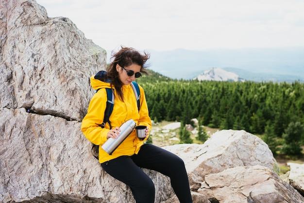 Девушка-туристка отдыхает после тяжелого подъема в гору. счастливый турист пьет кофе из термоса в зеленом лесу. путешественница пьет горячий чай из термоса в горах.