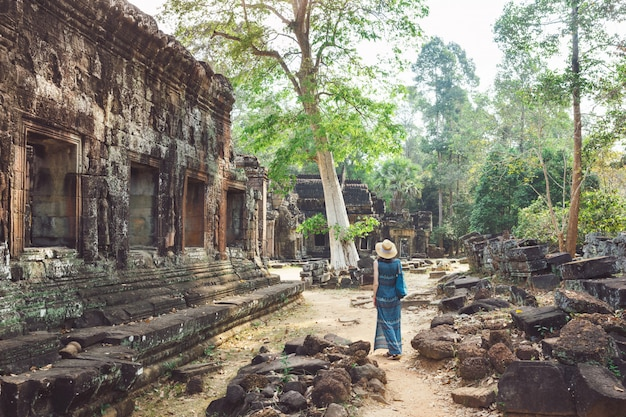Туристская девушка гуляет среди зданий древнего храма в ангкор, камбоджа.