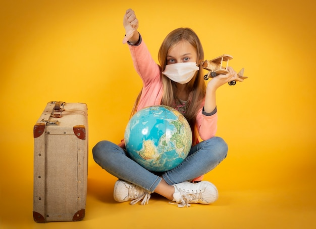 Девушка-туристка в медицинской маске, вспышка коронавируса covid-19. отмененная концепция путешествия. турист не может уехать из-за пандемии.