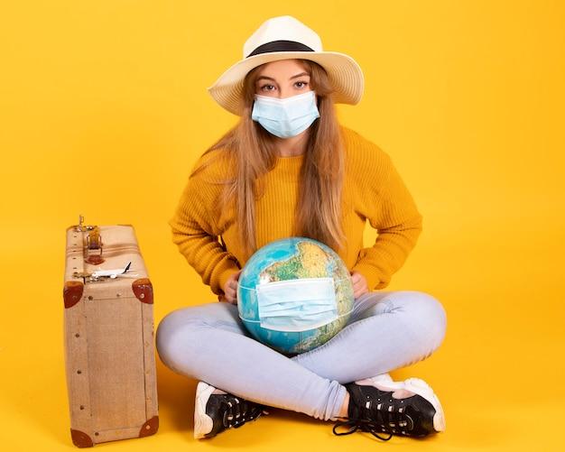 医療用マスクを持ったツーリストの女の子、スーツケース、地球儀を持って旅行に進んでいますが、covid-19はそれを防ぎます