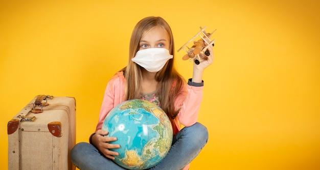 医療用マスクを持った観光客の女の子、コロナウイルスcovid-19の発生。キャンセルされた旅行の概念。パンデミックのため、観光客は立ち去ることができません。