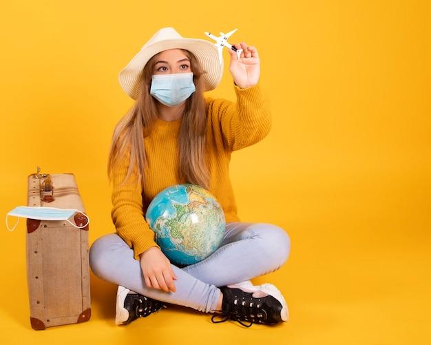 医療用マスクを持つ観光客の少女、コロナウイルスcovid-19の発生。キャンセルされた旅行の概念。パンデミックのため、観光客は出国できません。