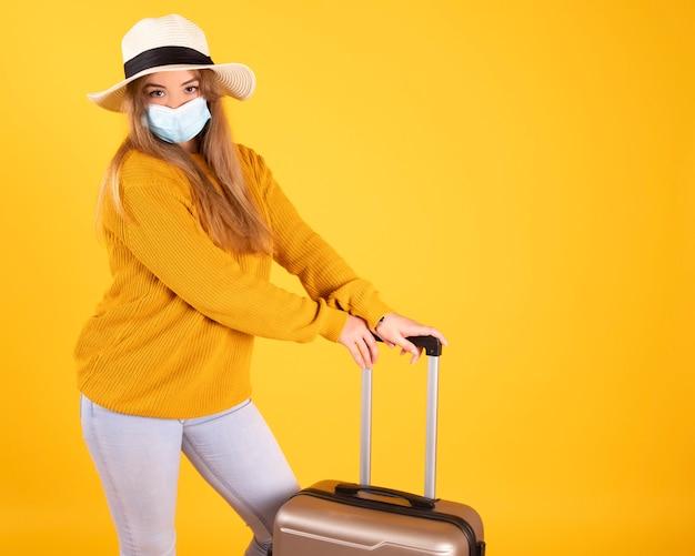 Туристическая девушка с медицинской маской, вспышка коронавируса covid-19. концепция отмененных поездок. турист не может уехать из-за пандемии.