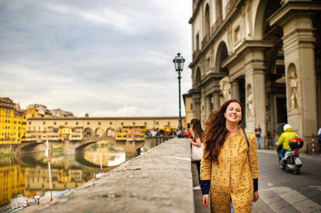 주황색 코트를 입은 관광 소녀가 이탈리아 피렌체의 제방을 행복하게 걷고 있습니다.
