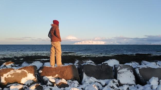観光客の男が冬にアイスランドの畑を歩きます。